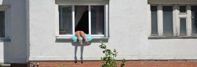 Nuda prende il sole sul davanzale della finestra, per i vicini, basta è troppo!